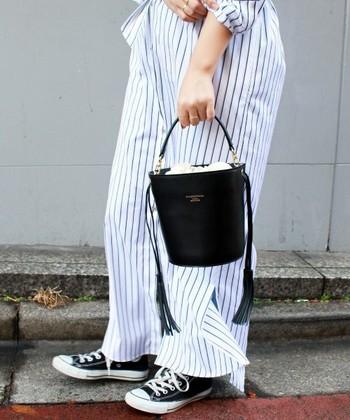 コットンのオールインワンに、足元はコンバース。バケツ型のバッグを合わせれば、大人っぽいコーディネートに仕上がります。