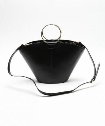 ゴールドのリング型の持ち手がアクセントになったバッグは、肩からも掛けられるショルダー付きなので、2WAYで楽しめ、コーディネートの幅が広がります。