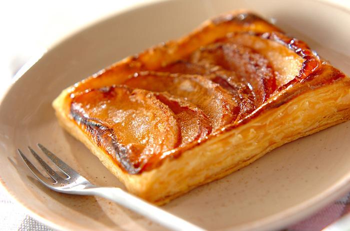 切ったパイシートに煮リンゴを乗せて焼くだけ。自然にパイ生地が立ち上がるので成形いらずの簡単アップルパイです。 最後にシナモンパウダーを振りかけて完成♪