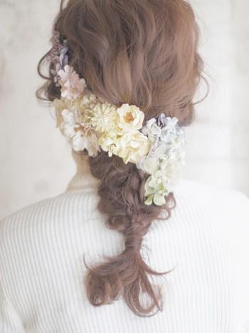 ゆるウェーブヘアを毛先まで丁寧に編みこんだ、編みおろしアレンジ。大きめの流れるようなお花のヘッドドレスを斜めに付けて、清楚で上品なウェディングアレンジが完成します。