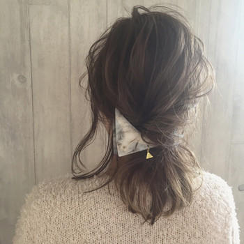 髪全体を低い位置でまとめて、ねじってヘアアクセサリーで留めるだけ。 控えめにしたい場合は、少し崩してあげるとナチュラルな雰囲気に。