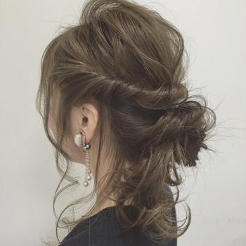 髪全体をランダムに巻いたら、サイドの髪を残し、トップの髪を低めの位置で結んでゆるめのお団子にします。 サイドの髪をねじってお団子の上でくるりんぱして崩し、くるりんぱした先をお団子の根元からて引き出します。 襟足の髪を左に寄せてお団子の根元に巻き付ければ完成♪
