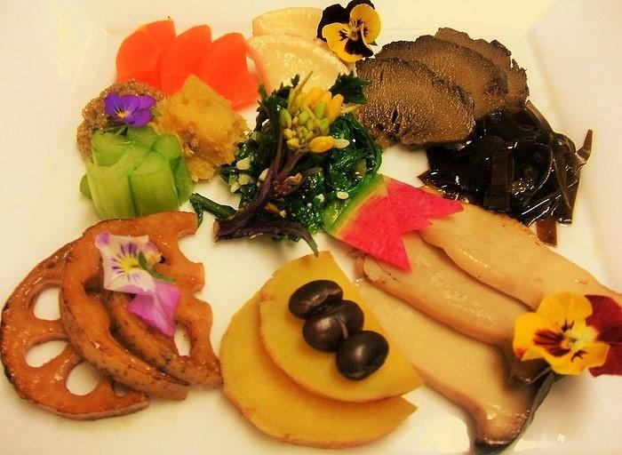 メニューは『自然食セット』『ベジミート唐揚げ』『ベジタブルカレー』『豆腐ステーキジンジャーソース』『ノルウェーさばの塩焼き』『エゾシカハンバーグ』。カレーには野菜が、カレー以外のすべてのメニューには玄米・味噌汁・野菜つき。 画像はお皿に盛りつけられた『自然色セット』の野菜たち。
