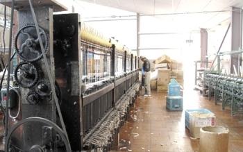 びわこふきんにも使われている「ガラ紡」とは、ガラガラと音を立てる大きな機械でゆっくりと糸を紡いでいく、昔ながらの紡績方法のこと。長い綿しか紡げない高速の紡績機と違い、ガラ紡は短い綿も無駄にせず、丁寧に糸に仕上げます。