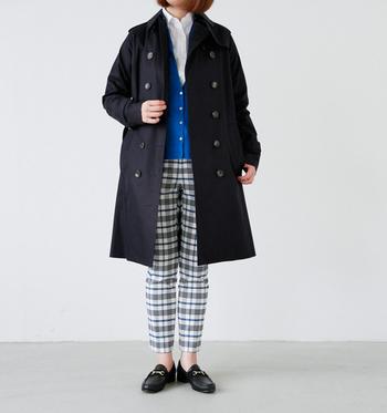 ダークカラーのトレンチコートは、色鮮やかなブルーのカーディガンを差し色に。インナーに白シャツ、チェック柄パンツを合わせたトラッドなスタイルです。
