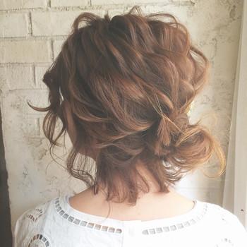 髪の毛をコテで挟み、内巻き&外巻きを交互に繰り返していくだけでパーマをかけたようなウェーブヘアに。 仕上げにくるっとお団子にすればOK。襟足の後れ毛が出ていた方がルーズ感があって可愛いですね。