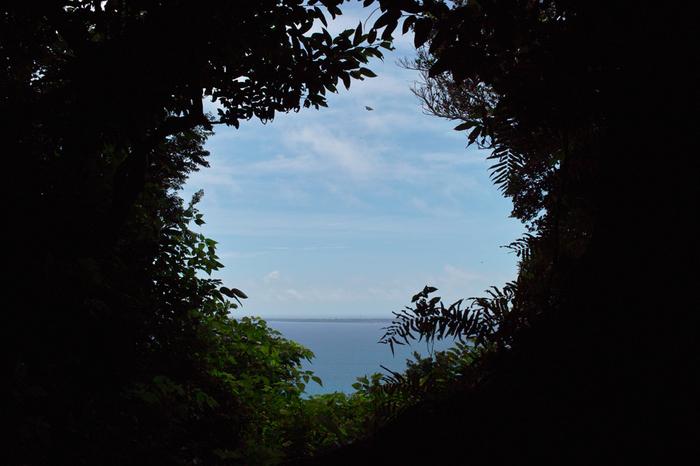 """山庫理からは、神の島「久高島」が拝めます。久高島は、海のかなたの異界""""ニライカナイ""""につながる島として崇められてきました。心が浄められるような神々しい光景が海の向こうに広がります。"""