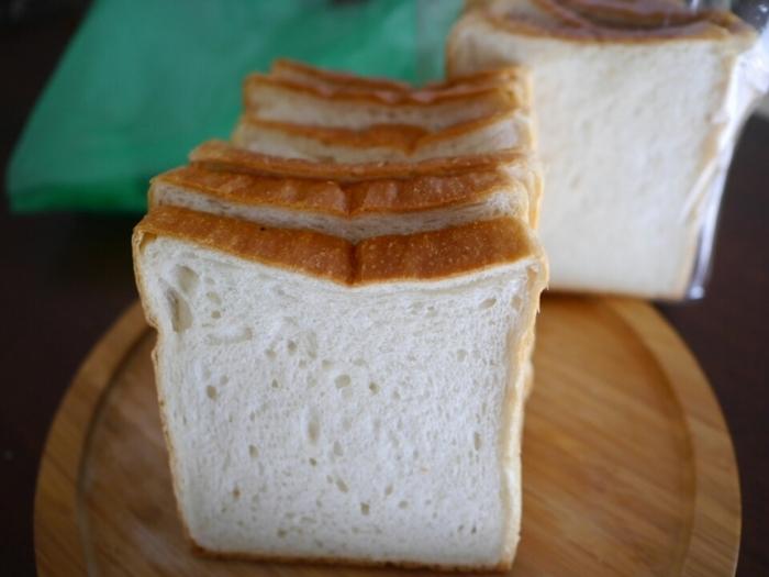 シンプルな角食パン。こちらは無添加ドライイーストを使ったこだわりの製法ゆえに1日の量に限りがあり、行列ができるほど大人気の定番商品です。常連さんで一度に4~5斤以上も買われる方もいるそうで、入手が困難とも?!