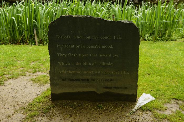 ワーズワースの詩「水仙」の一部を刻んだ石碑。石碑の周りには水仙が並び、その後ろには石造りの橋とカフェが見えます。