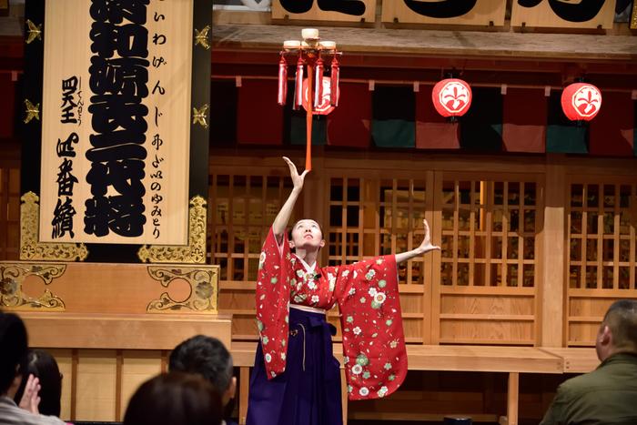 """ボールや枡(ます)などを開いた傘の上で転がす""""傘回し""""、口に咥えた棒の先に茶碗を立てる""""五階茶碗顎""""などの日本古来の太神楽曲芸も鑑賞することができます。"""
