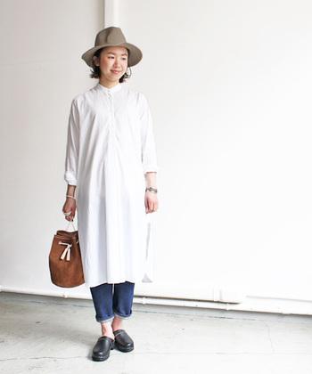 スタンドカラーが珍しいシャツワンピースは、きちんと上までボタンを締めて着こなしましょう。長めの丈ですが、横にスリットが入っていて軽快に歩けます。そのまま1枚でさらりと着るも良し、写真のように下に細めのジーンズを履くのも素敵。
