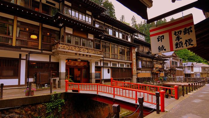 大正から昭和にかけて建てられた三層四層の木造旅館が、銀山川の両岸に軒を連ねる「銀山温泉」。スタジオジブリの長編アニメーション映画『千と千尋の神隠し』のモデルになった温泉街ともいわれています。朱色の橋の先に立つのは国の重要文化財に指定されている「能登屋旅館」です。