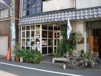 """中野通りの五差路の近く、看板に引き寄せられて少し脇道に入ってみると、カフェのシンボルマーク・にわとりの絵が描かれた旗が見えてきます。らんぱだⅡは、作る人も食べる人も安心・安全な""""フェアトレード""""のオーガニック食材を使ったオリジナル料理や飲み物が味わえるお店です。"""