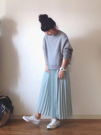 シンプルな無地のスウェットは、少しオーバーサイズのものを選んでゆったり感を。爽やかなブルーのプリーツスカートと合わせて、女性らしいシルエットのコーデに。
