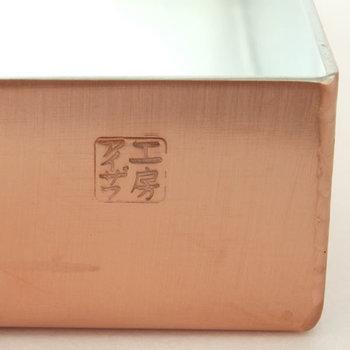 大正11年創業の老舗「工房アイザワ」の印が捺された純銅製の玉子焼き器。内寸9cm×15cmというコンパクトなサイズなので、玉子1個からでも無理なく巻けるのが特徴。毎日のお弁当作りにもぴったりです。