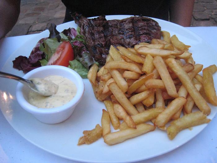"""ステーク・フリットはステーキとフライドポテト、というそのままの意味でそのままのひとさらです。えっこれがフランス料理?と思うかもしれませんが、フランスのカフェなどでどこでも食べることができる超定番メニュー。モモやフィレなど、霜降りではない赤身の肉肉しいお肉を塩胡椒でシンプルに焼き上げ、たっぷりのポテトを添えていただくのですが、これがなんともクセになります。フランスに初めて訪れると、フランス人のフライドポテト好きにびっくりするはず。英語でフライドポテトのことを""""フレンチ・フライ""""と呼ぶのも納得です。  ■材料 ・赤身ステーキ肉 お好きなボリュームで、一人一枚 ・フライドポテト 適量 ・バター・パセリ 適量 ・塩・胡椒 適量  ■作り方 1. 塩・胡椒したステーキ肉をグリルで好みの焼き加減まで焼く。 2. お好みでバターで香ばしさを出したたっぷりのフライドポテトと一緒に盛り付ける。 3. パセリを散らしていただく。"""