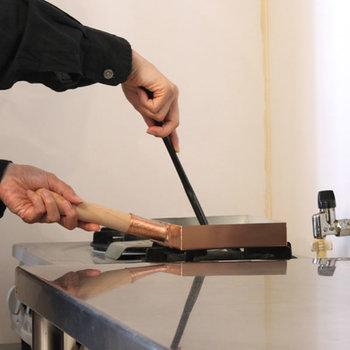 3:空いた部分に再度油をしき、巻いた卵焼きを奥側に滑らせます。 手前にも油をなじませ、残った卵液の約1/3を流しこみます。卵焼きを菜箸で持ち上げ、卵焼きの下にも卵液を流しいれます。半熟状態になったら、奥から手前に向かって卵を返します。