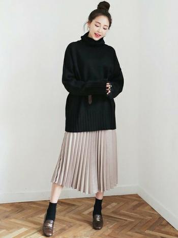 オーバーサイズのニットと、シルキーなプリーツスカートの組み合わせ。程よくリラックス感がありつつ、女性らしさもしっかりキープ。
