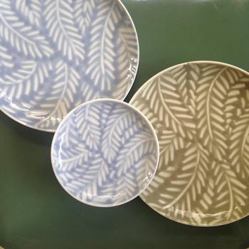 美しい草の葉模様の平皿は、見ているだけで溜め息が出ちゃいますね。この繊細な手仕事で作られる陶器は、陶芸作家「内村七生(うちむら なお)」さんの手によるものです。