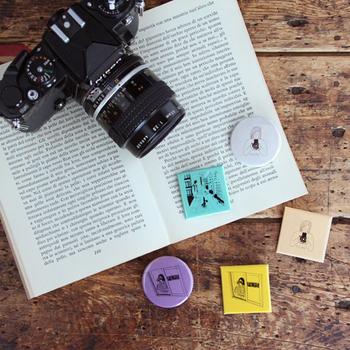 カメラ周りの雑貨を扱いながら、写真の楽しみ方を伝えるお店「monogram」が、フィルムカメラに興味がある人々をつなぐ活動として立ち上げた「FILMS」という企画。その関連グッズとして作られたのが、こちらのポップな缶バッチ。これを付けていると、何となくフィルムカメラ好きなんだとアピールできちゃう。カメラバックのチャームとして付けてみてもいいですね。