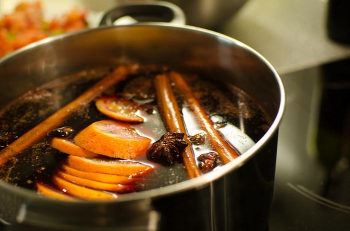作り方① 鍋に赤ワインを注ぎ、スパイスとオレンジの皮を加えて弱火にかけます。