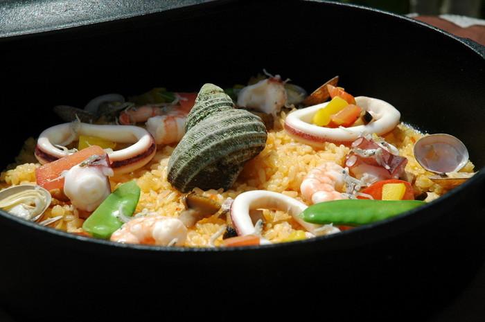 地元で獲れる新鮮な魚介と季節のお野菜で「島のパエリア鉄鍋風」。おこげまでも美味。
