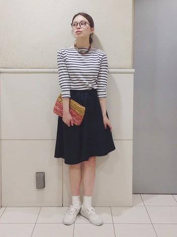 ボーダーTシャツにスカートは王道のスタイルですが、ネックレスやクラッチバッグ、メガネの小物づかいがとってもおしゃれ。