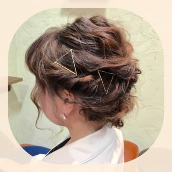 トップからゆるくウェーブを作ってアップにした髪にゴールドピンの三角をいくつもアレンジしています。さりげない髪飾りなので、お着物にも似合いそうですね。