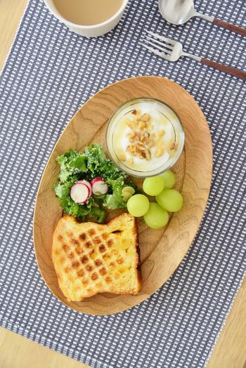 木製のお皿には、焼き立てパンとガラス製の器に入れたヨーグルトがよく似合います。パンとヨーグルトの間に緑の葉物やフルーツを置くことで、カフェ風のスタイルに近づきます。