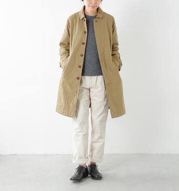 ベージュのステンカラーコートにホワイトパンツを合わせた春らしいスタイル。メンズライクシルエットのアイテムは、裾をロールアップしたり着こなしを工夫して。コートのアイコニックなボタンもコーディネートのポイントになっています。