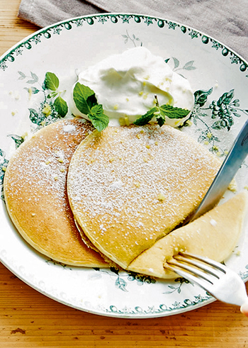 レモンの皮のみじん切りを混ぜ込んだ、レモンが香る爽やかなレシピ。牛乳多めのミルクパンケーキは、ほんのりとした優しい色合いに焼き上がります。クリームを添えて召し上がれ!