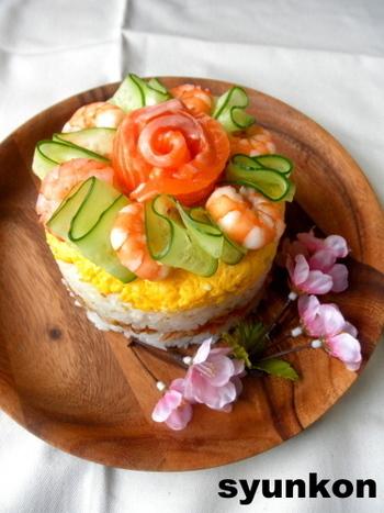ケーキ型を利用して作るちらし寿司ケーキ。サーモンやキュウリの飾り方が参考になります。酢飯と具材を交互に重ねていくと横から見ても綺麗な仕上がりに♪ごはんに色を付けて三色にしてみてもいいですね。