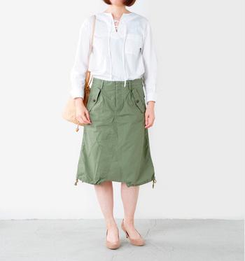 襟元のVカットが美しい白ブラウスを、グリーンのカジュアルなスカートにイン。足首を細く見せてくれるヌーディーなパンプスや、同色のバッグを合わせて大人っぽくまとめてみましよう。