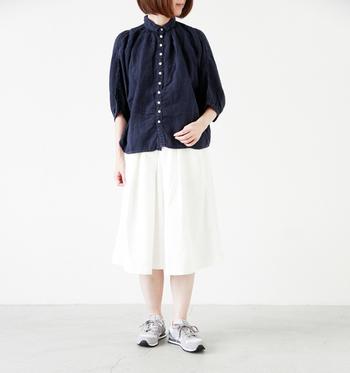 五分丈の紺色のナチュラルなリネンシャツに膝下スカート+足元はスニーカー。小さな襟のものやギャザー入り、パフスリーブやドルマンスリーブタイプのシャツを選べばより女性らしい雰囲気に。