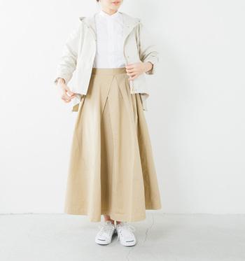 ベージュロングスカートに白シャツをイン。アイボリーのフード付きジャケットを羽織り、足元は白スニーカーをあわせて。春らしさあふれる、大人可愛いナチュラルコーデの完成です。