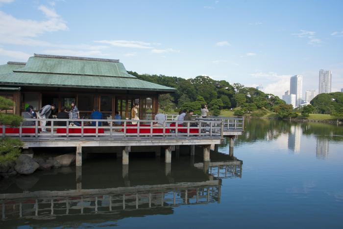 昭和58年に再建された御茶屋は開放的な作りと鮮やかな毛氈が印象的で日本らしい佇まい。広がる池と緑、遠くのビル群を眺めながら一息ついて。