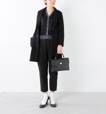 黒のトレンチコートを合わせたモノトーンスタイル。オールブラックの中に、カーディガンのグレーのラインがタイルアップして見せてくれていますね。パンプス+ソックスで女性らしい抜け感のある足元に仕上げています。