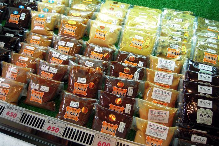 「大阪屋こうじ店」は、舞鶴に本店がある老舗の糀屋。市内には三条神宮にお店があります。 店舗には、麹各種の他、甘酒やもろみ、手作り味噌のキット等、様々な商品が並び、老舗麹店ならではのラインナップ。味噌も白、赤、麦、八丁と各種揃い、白味噌も、普段使いに向く、米麹2割5分で仕込んだ「白甘味噌」、京料理、雑煮向きの3割仕込の「京白味噌」と2種あり、西京漬専用の味噌もあります。