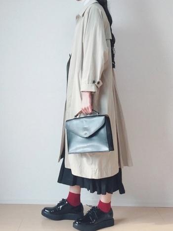 プリーツスカートにロングのコートを合わせた上級者コーデ。裾からチラリとのぞくヒラヒラプリーツがオシャレ。赤のソックスが差し色になっていますね。