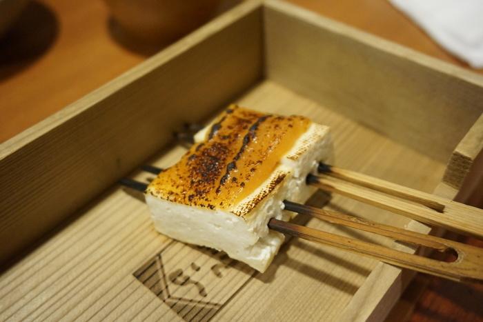 """【「田楽豆腐」は、京の食文化形成、真髄を端的に示す食物かもしれません。  平安末期に中国から豆腐がもたらされると、拍子木切りにし竹串を打って焼き上げた豆腐が誕生しました。鎌倉から室町時代にかけて、隙間なく摺り目が付いた「すり鉢」が調理道具として普及し、「味噌」をすり潰して調味料として用いるようになり、やがて焼いた豆腐に味噌をつけた料理が流行しました。「田楽豆腐」の名は、田の神を祀って豊作を祈願する「田楽(日本の伝統芸能)」の踊り手である""""田楽法師""""に由来し、豆腐の姿が、白袴を穿いて一本足の高足に乗って踊る法師に似ていることから、その名がついたと云われています。  「田楽味噌」は、豆腐以外の素材にも用いられ、京都では生麩や里芋、茄子や万願寺とうがらし等がよく使われています。また一般的な「田楽味噌」は、味噌にみりん、砂糖、水を加え、煮詰めて作りますが、京都では、季節や食材に応じて、白、赤、合わせ味噌を用い、柚子や山椒、木の芽や唐辛子等の香味を加え、様々なバリエーションの田楽味噌を作ります。 (画像は、南禅寺「順正」の豆腐田楽)】"""