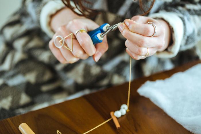 こちらは「tou(トウ)」という名のネックレス制作場面。直線に切り出した木材や、まん丸に焼いた陶など、自由な発想の組み合わせです