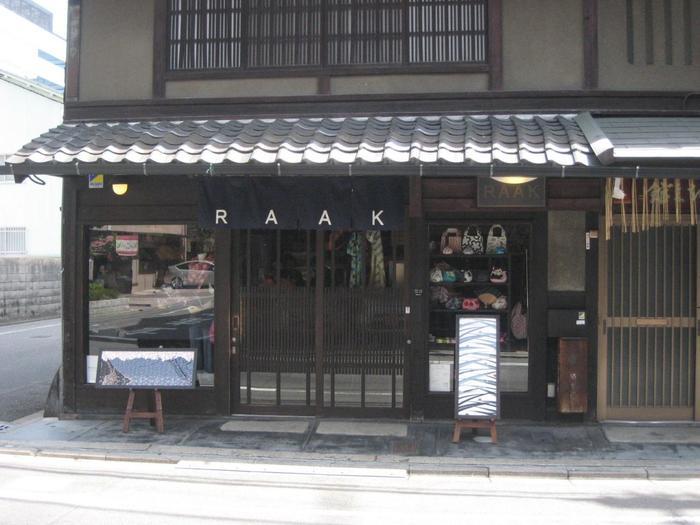 「永楽屋 細辻伊兵衛商店」は、京都らしい伝統柄の手拭や布小物を取り扱う、京都で十四代、400年に渡って商いを続ける日本最古の老舗綿布商。その永楽屋から2004年にスタートした「RAAK」は、伝統を生かしながらモダンなデザインやユーモアを取り入れた新しいブランドラインです。RAAK本店は、町歩きの途中立ち寄るのにちょうど良いところに、町並みに馴染んでさりげなく佇んでいます。地下鉄烏丸御池駅からすぐです。