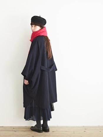 ゆったりとしたシルエットが可愛らしいケープ型コート。 全体をブラックでまとめあげたシックなスタイルに、首元の赤いマフラーがよく効いています。