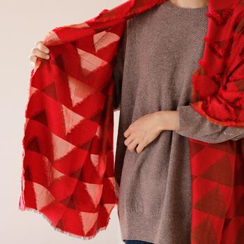 三角の連なる模様はフリンジで描かれています。織り上げた糸を部分的にカットし、布地の厚さに差を生み出して布に立体感を与えています。
