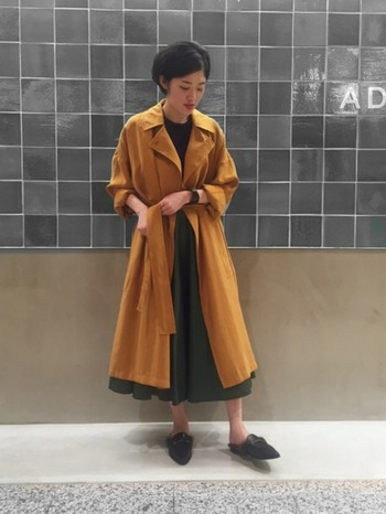 ぱっと目を引くビタミンカラーのコート。ビックシルエットで、無造作にさらっと羽織っても素敵です。裾から覗く、グリーンのスカートが足元に軽やかな動きを演出しています。