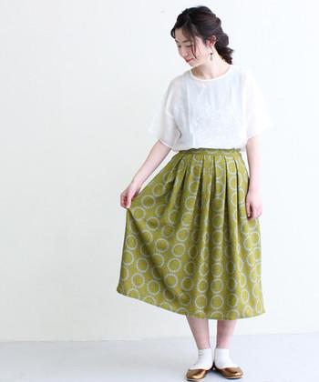 花の王冠のような優しい丸柄のフレアスカート。少しグリーンがかったイエローで、野原に行かずともお花畑の中にいるような気分になります♪