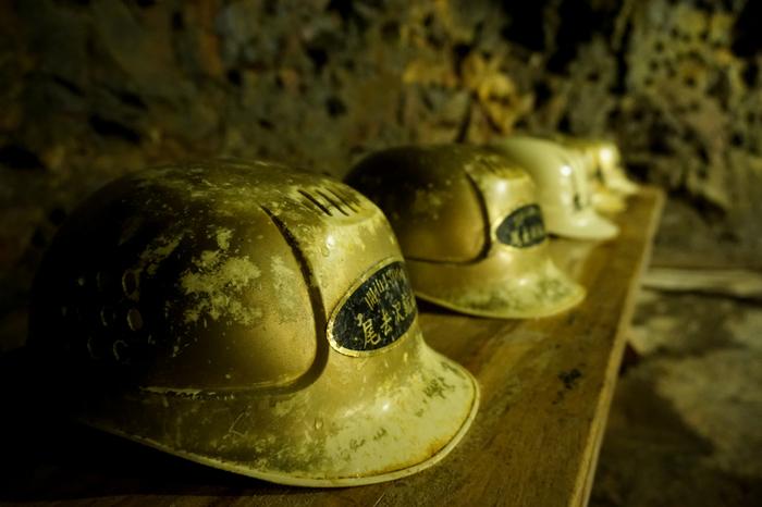坑夫たちが使用していた傷だらけのヘルメットが、尾去沢鉱山の栄光を静かに物語っており、ノスタルジックな雰囲気を醸し出しています。
