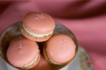 【春の味わいを存分に?桜色マカロン】 ピンク色のマカロンは、春の桜をイメージさせてくれますね。ホワイトチョコのガナッシュと淡いピンクの色合いが、さらに春らしさを演出してくれています。トッピングにのせるお塩が、全体の甘さを引き出す役目を果たしてくれますよ。