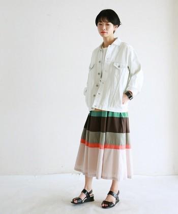 ビッグシルエットのデニムジャケットも、ホワイトだと爽やかな雰囲気に。上半身をシンプルにまとめることによって、春らしいマルチカラーのスカートが引き立ちますね。