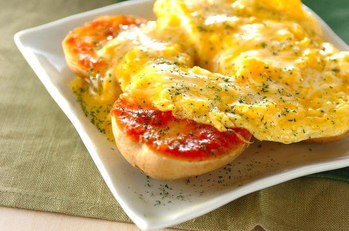 新ジャガが出まわる季節におすすめ◎電子レンジで6分ほど加熱したジャガイモに、ピザ用ソースを塗ります。溶き卵にはチーズを加えて、まろやかさをプラス。器に盛ったジャガイモに、フライパンで半熟に仕上げた卵を乗せればできあがり♡